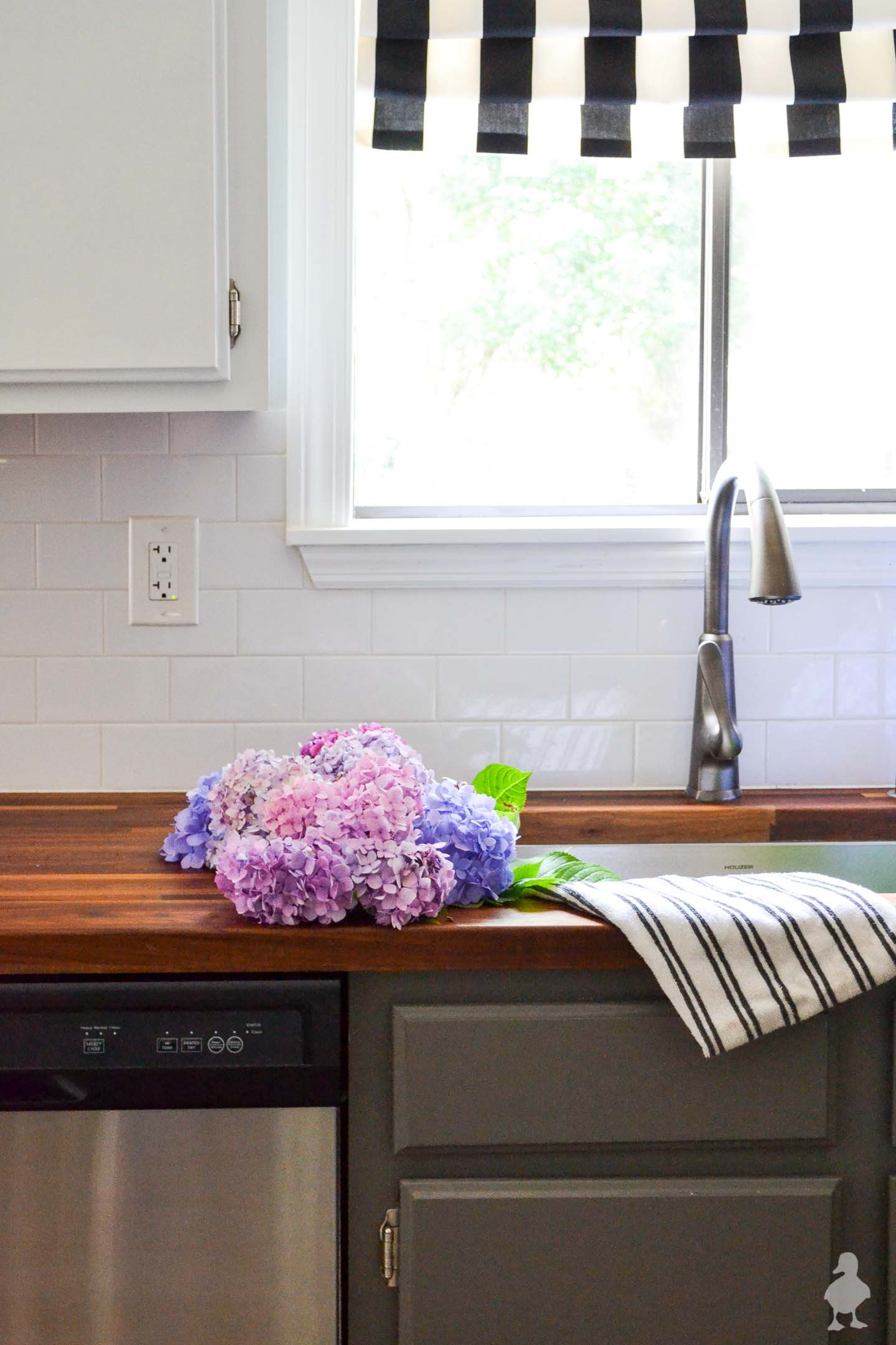 closeup of butcher block counters and sink with pink and purple hydrangeas