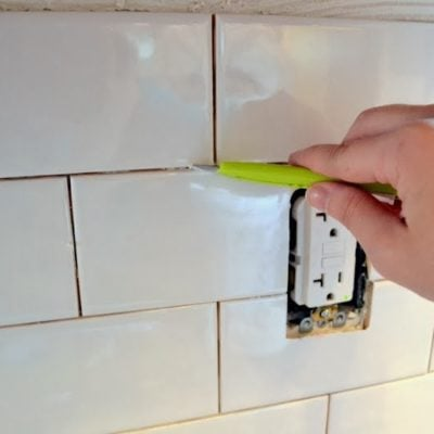 clean tile adhesive from grout lines with a small utility knife