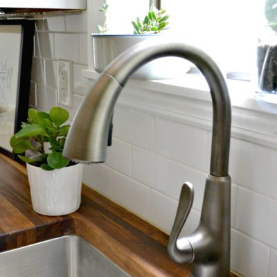 closeup of faucet next to butcher block