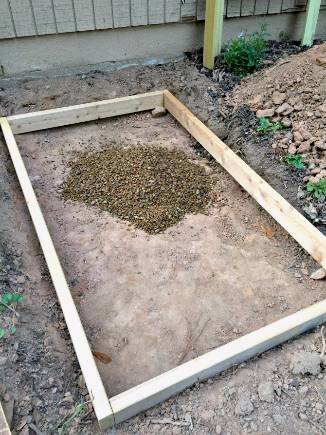 pile of gravel inside of 2x4 frame for concrete slab