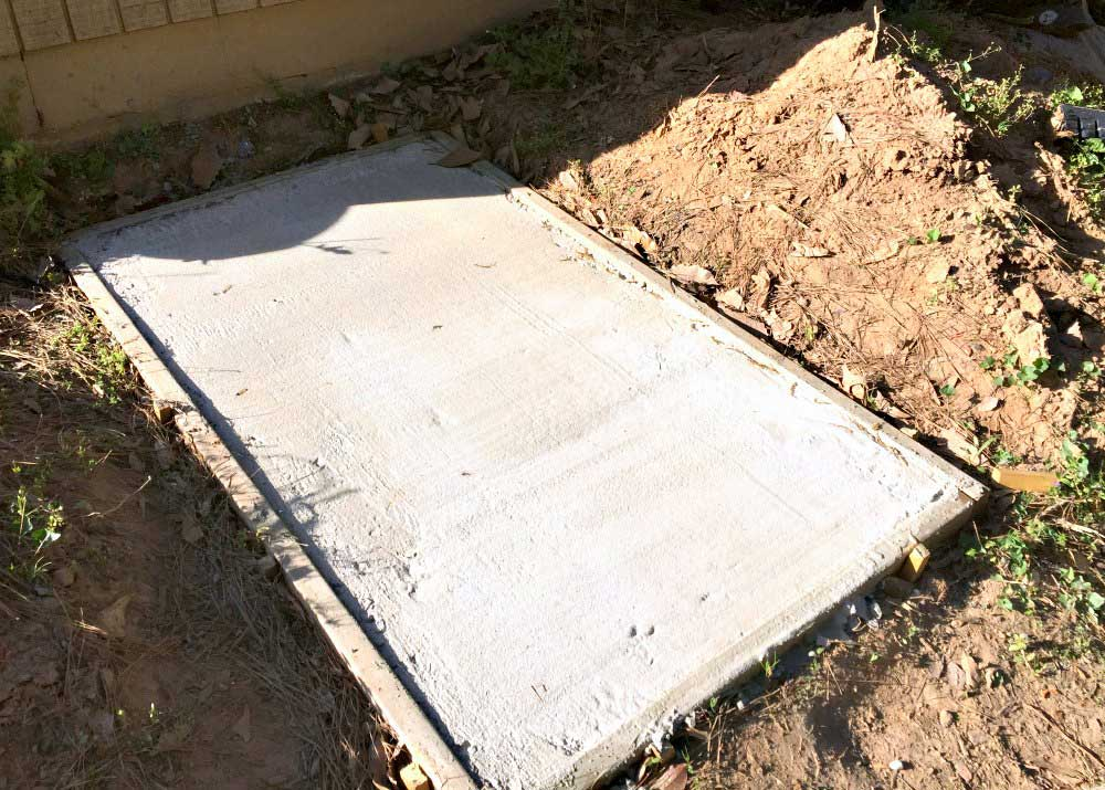 concrete slab poured for trash bins on the side of house