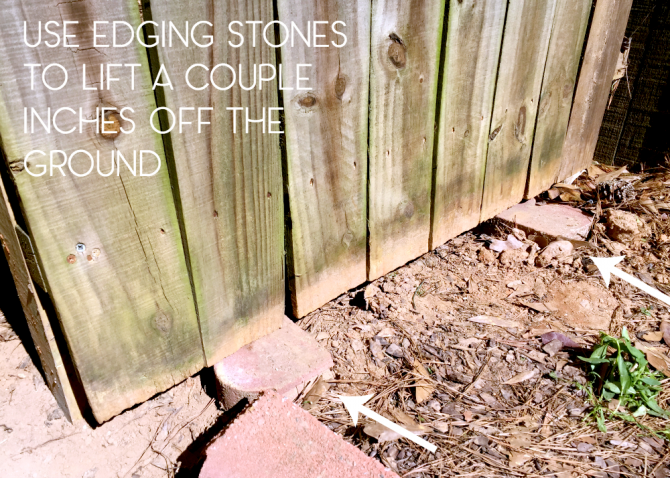 use edging stones to lift the fence panel off the ground