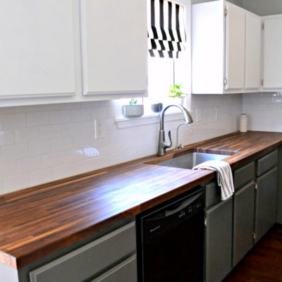 2014 kitchen - white upper cabinets, gray lower cabinets, black appliances, butcher block counters
