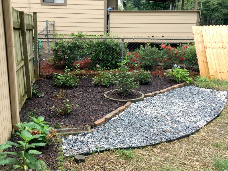 Hydrangea corner garden with new gravel and stonework - wet gravel