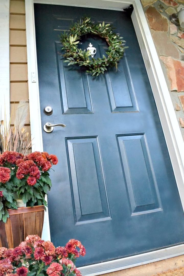 fall front door with new wreath and red mums