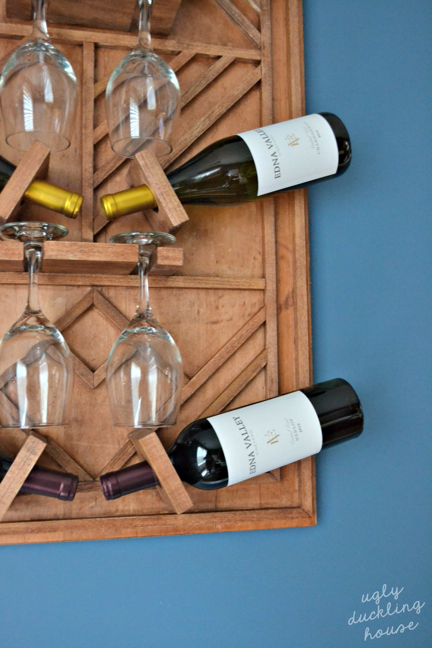 loaded wine rack with Edna Valley Vineyard and wine glasses
