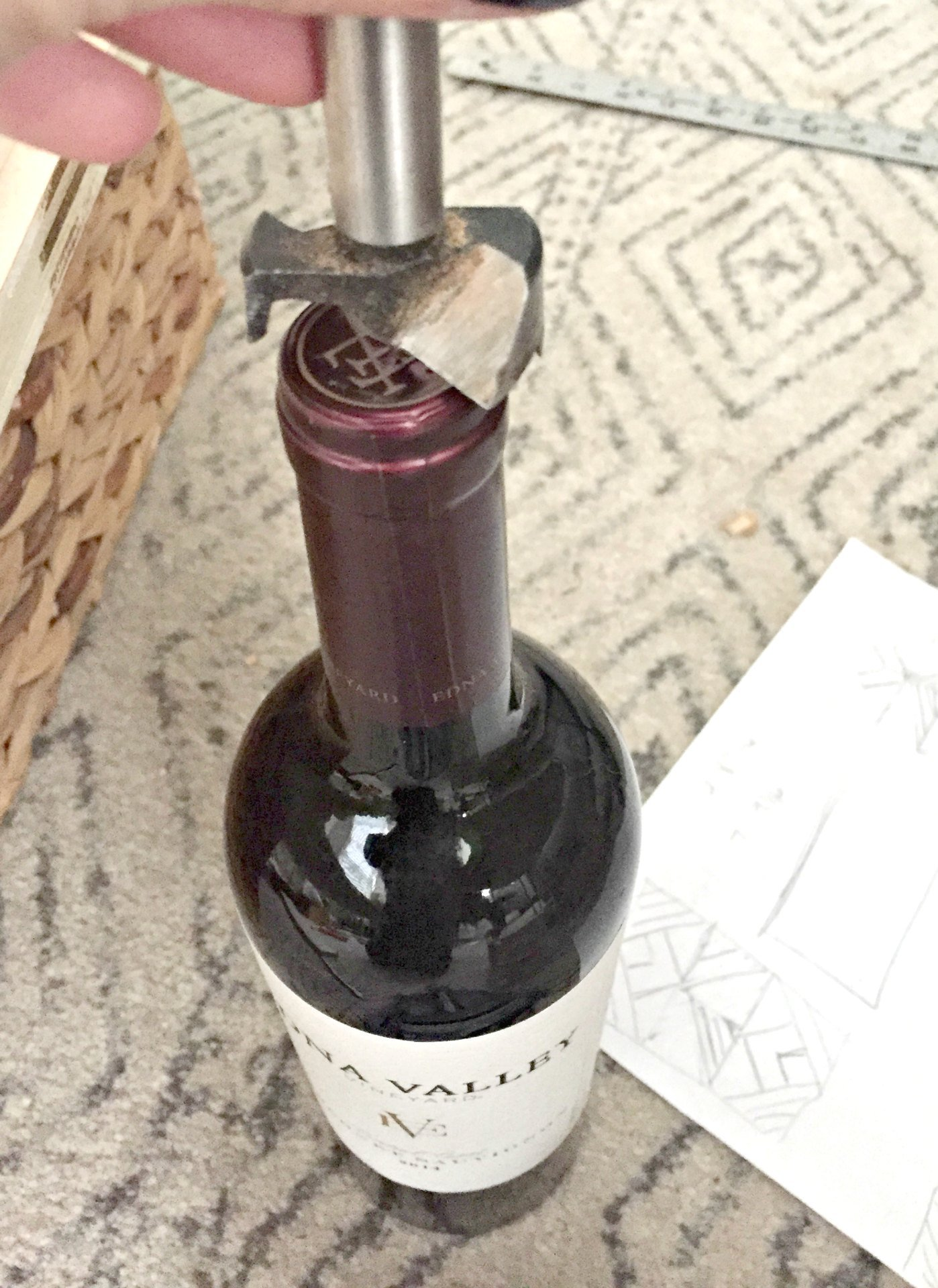 visually testing drill bit hole size on wine bottle