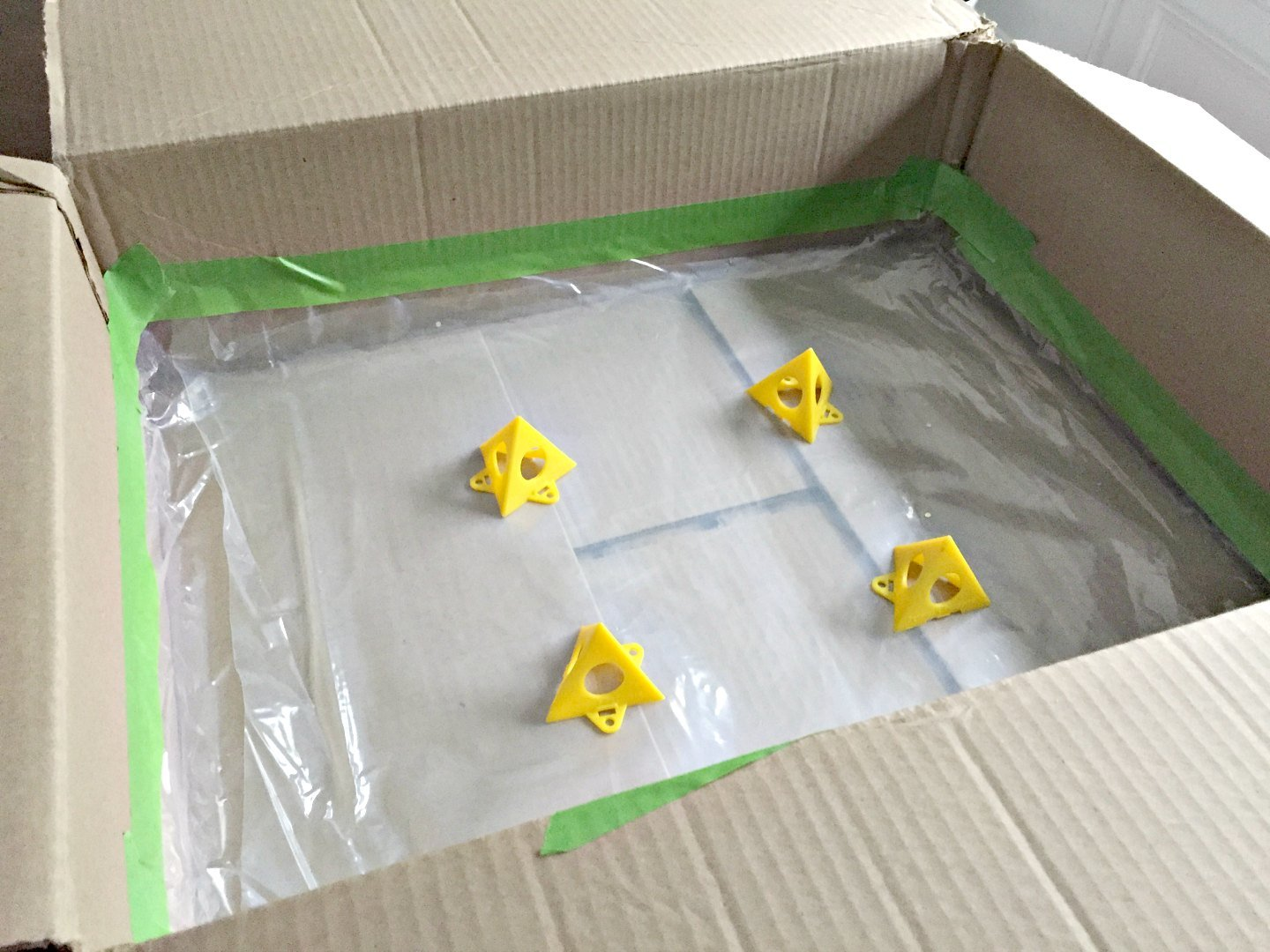 cardboard box with plastic lining and plastic pyramids to support painting
