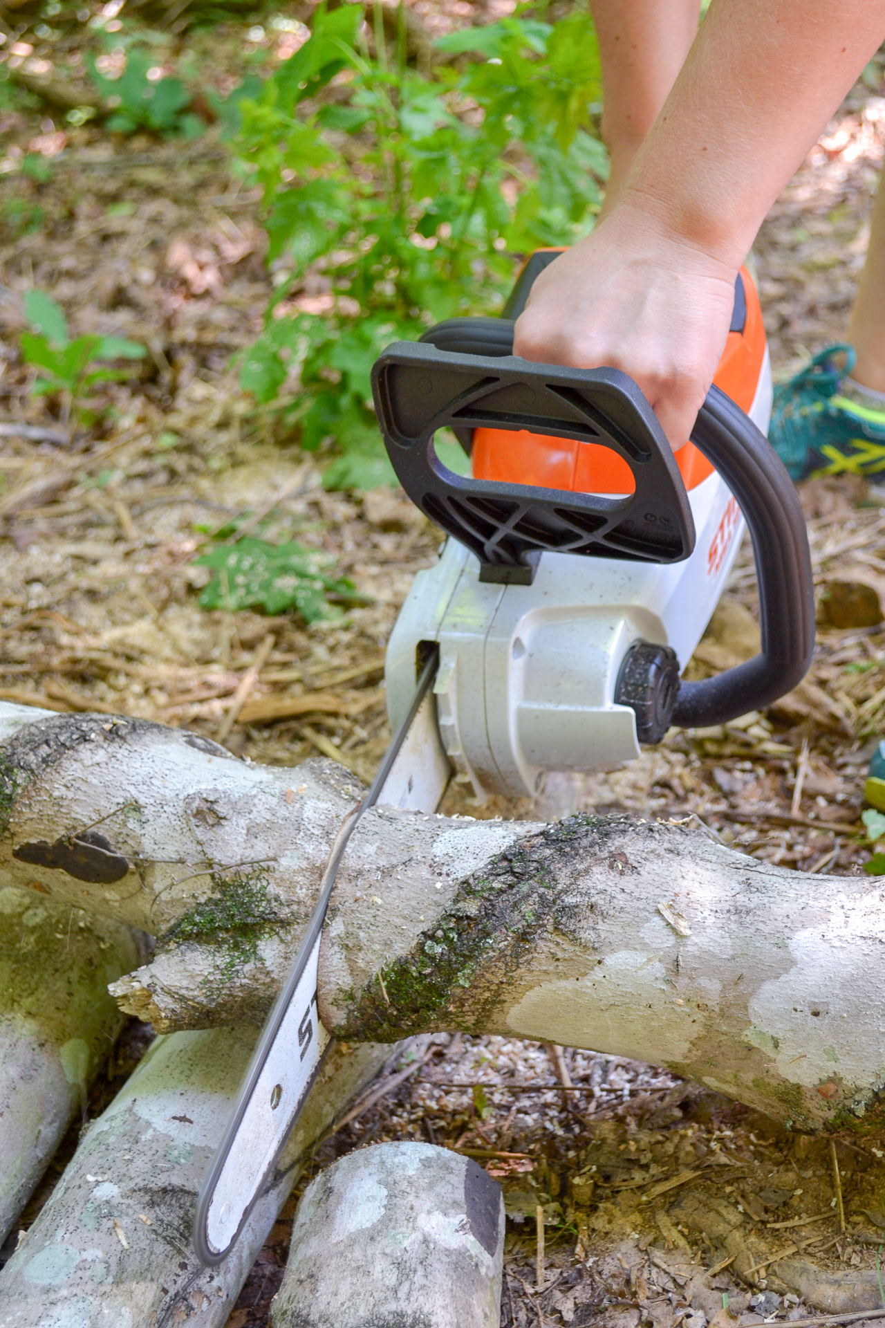 Another angle STIHL chainsaw cutting through log