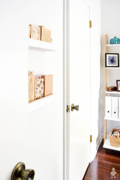 white doors inside office with picture ledges and bookshelf