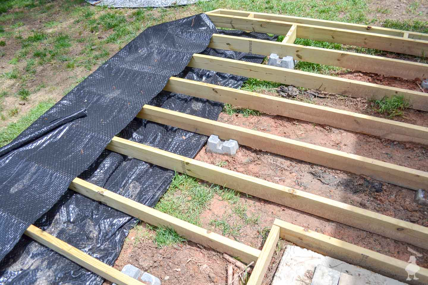 add in landscape fabric under floating deck