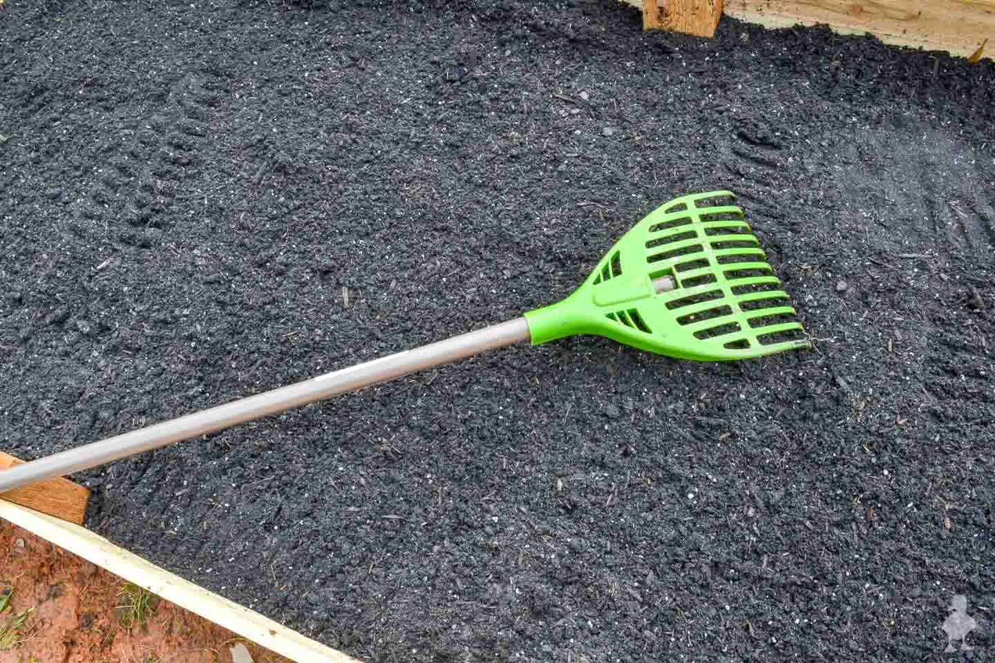 garden bed soil with green rake