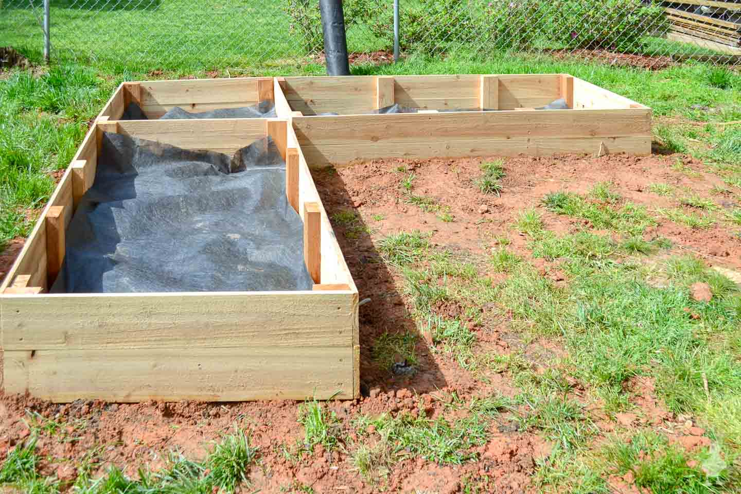raised garden beds with landscaping fabric lining bottom