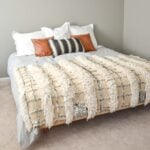 floating king bed with gray comforter white pillows leather pillows tribal pillow and moroccan wedding blanket