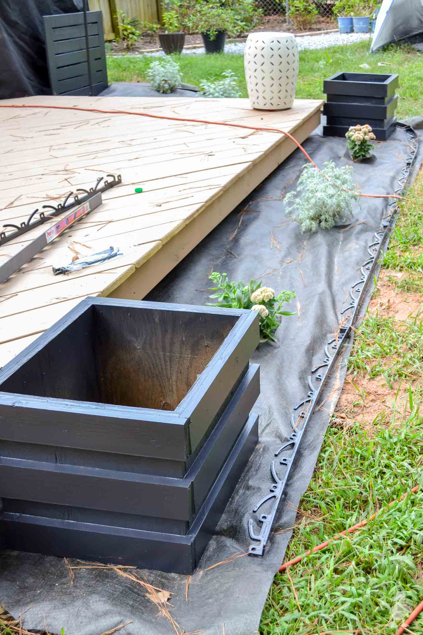 new black planters with landscaping around deck