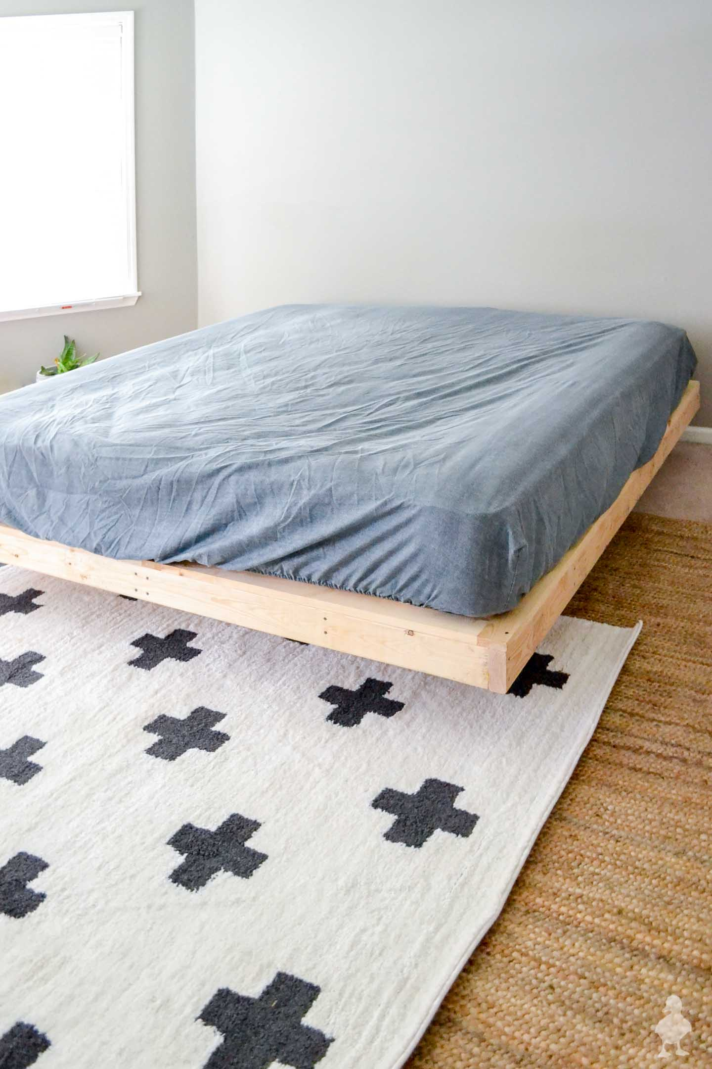 plus sign rug under floating bed frame