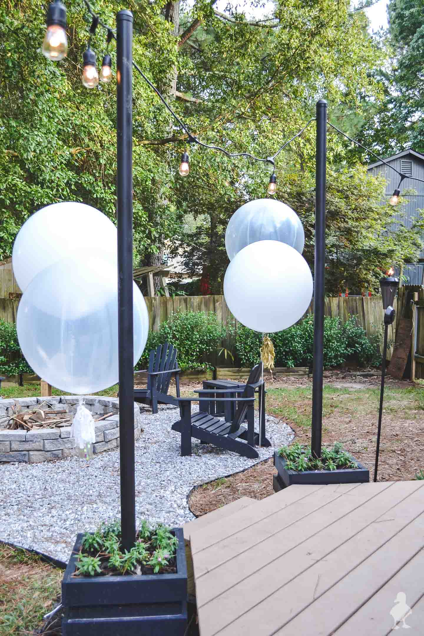 backyard light poles with black chairs around fire pit