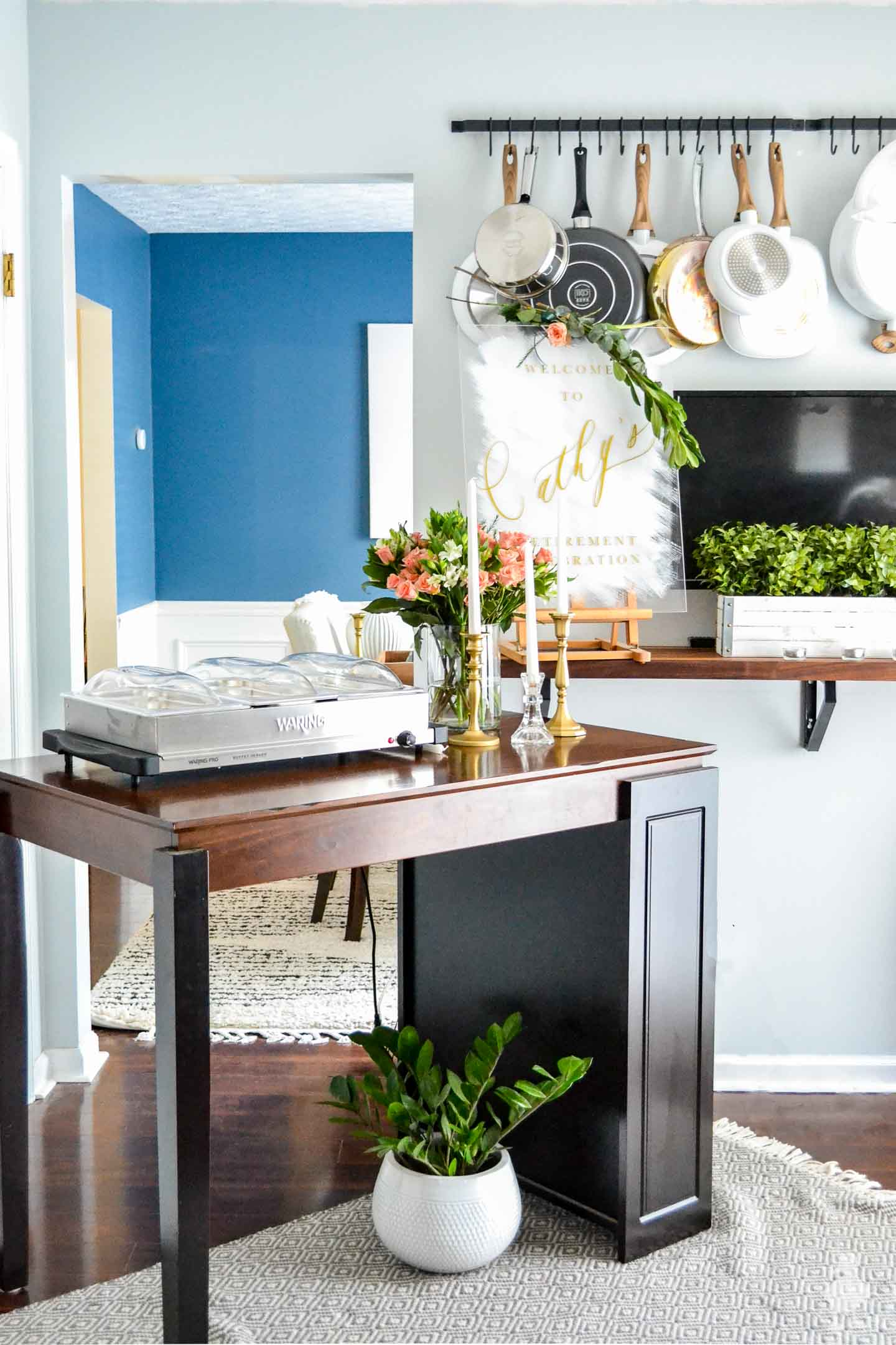buffet setup on table with blue kitchen walls and dining room