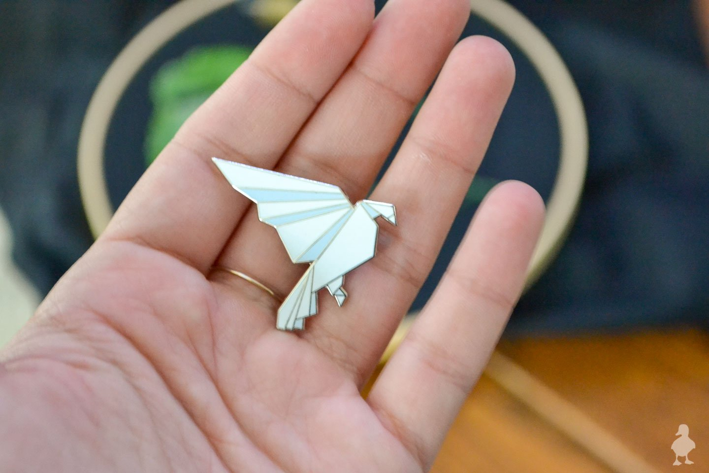 holding white origami lapel pin