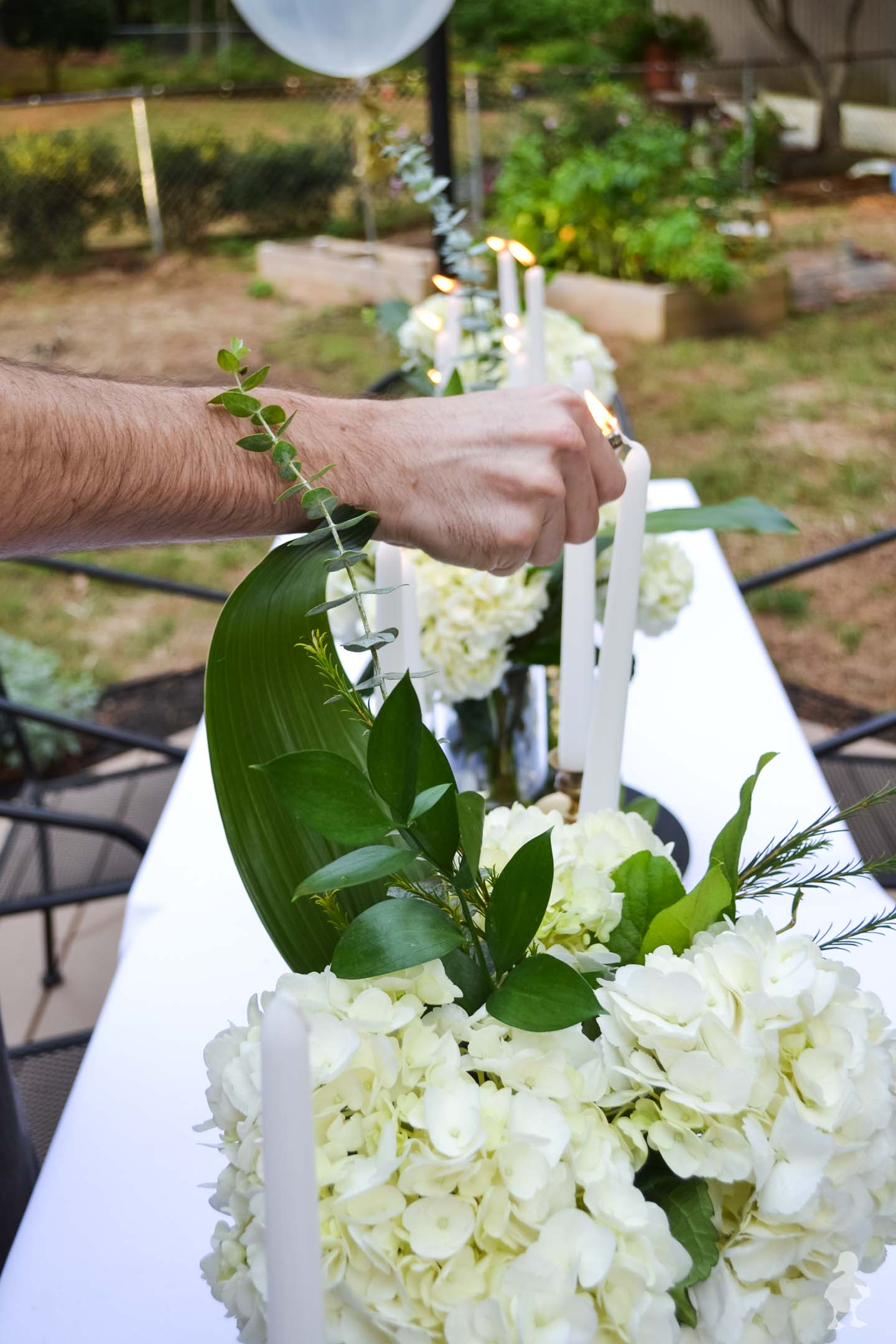 lighting candles with white hydrangea bouquets on long white table
