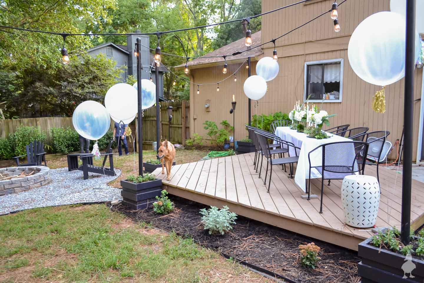 tan floating deck with landscaping white table white balloons hanging lights
