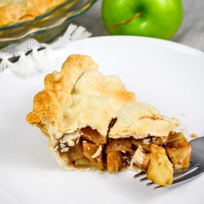 classic brandy apple pie slice on white plate with granny smith apple