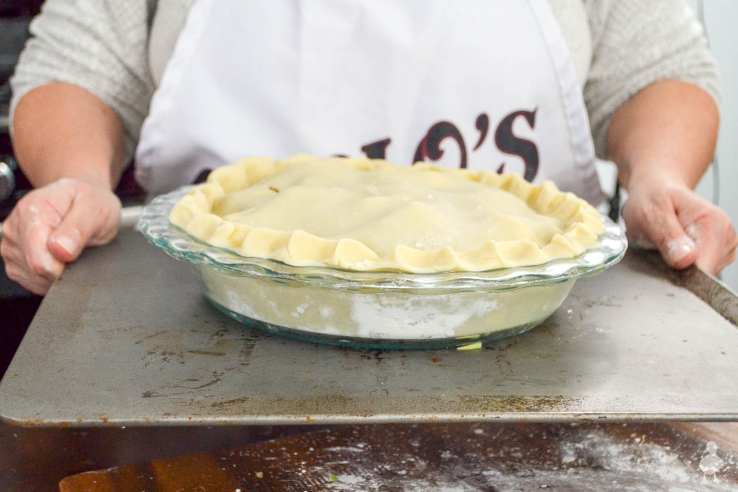 mom holding pan with apple pie ready to bake