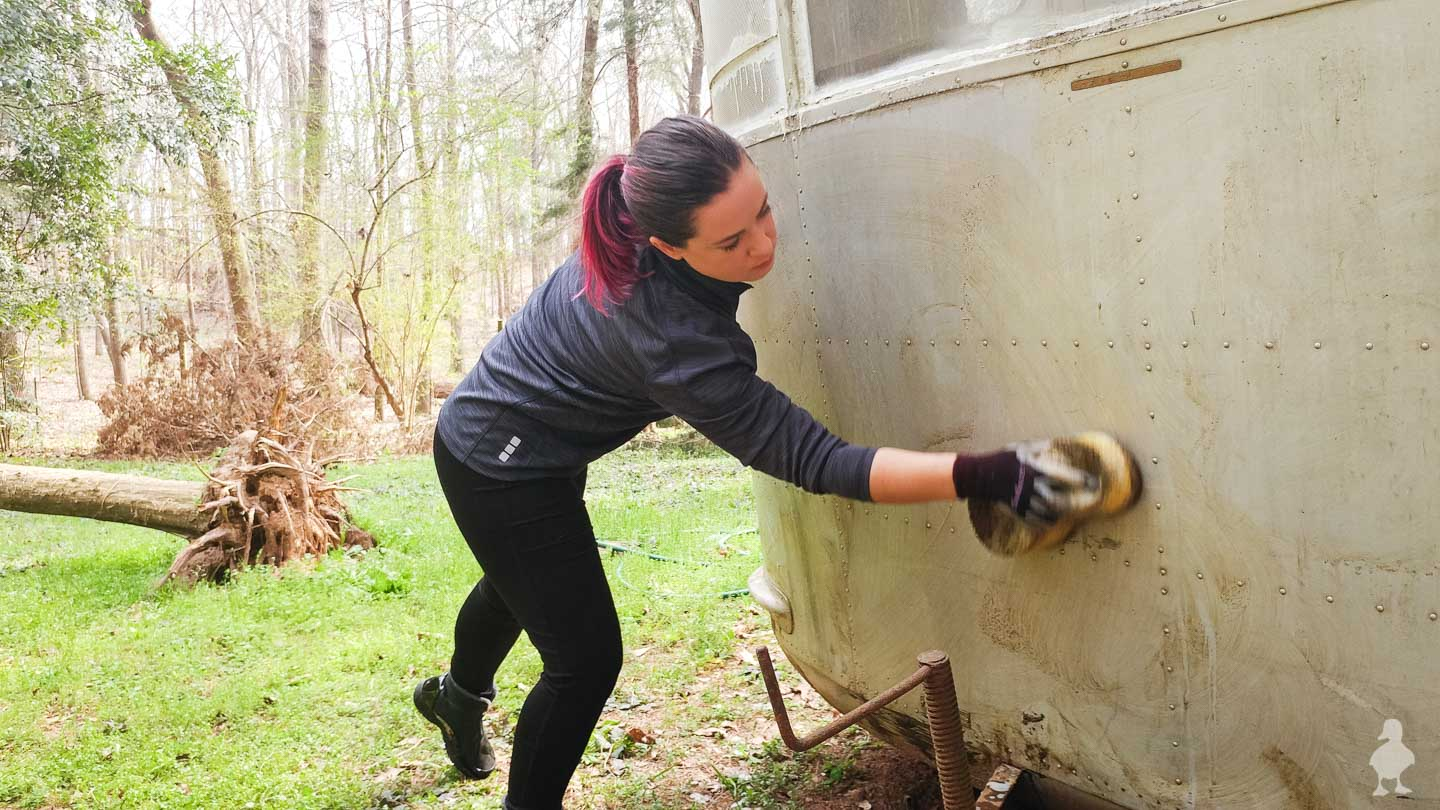 Sarah hand washing the vintage camper exterior