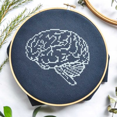 white anatomical brain cross stitch on black fabric flatlay