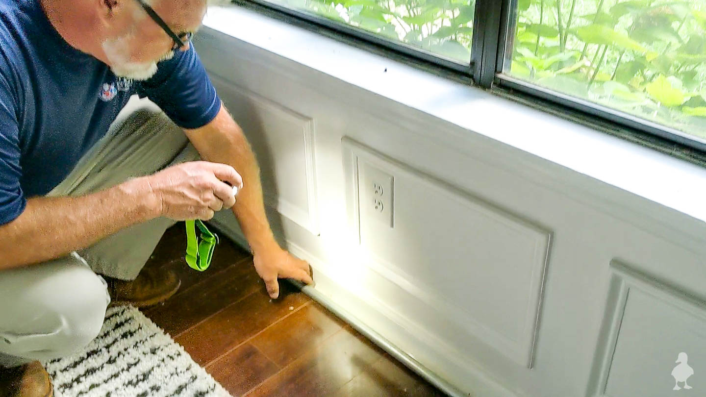 American Pest Control inspecting inside of house along foundation