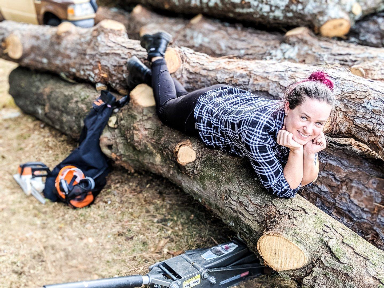 Sarah laying on wood logs