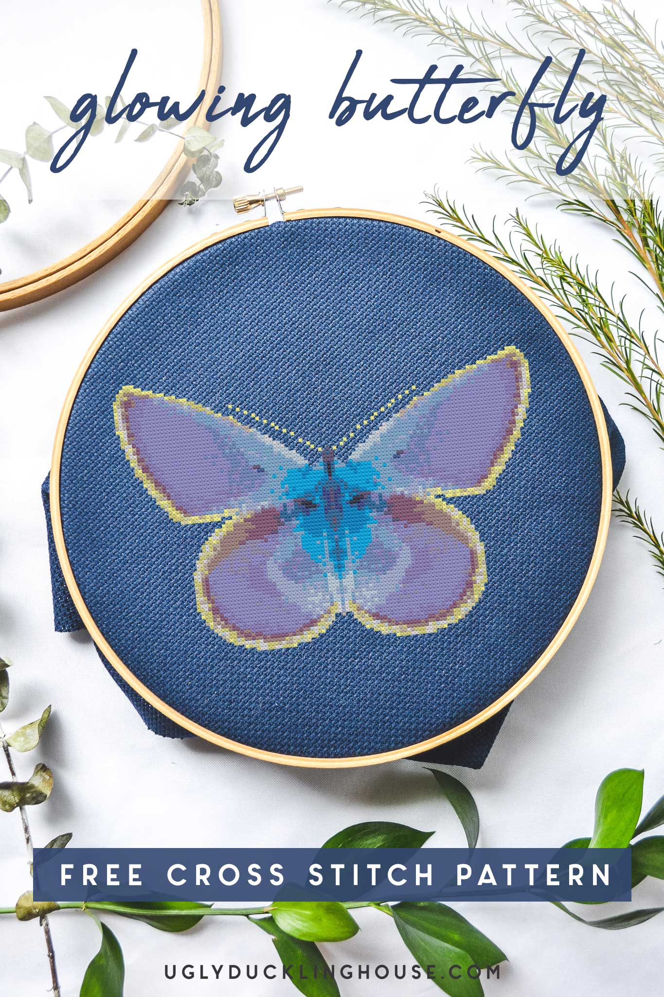 glowing butterfly cross stitch on navy embroidery hoop