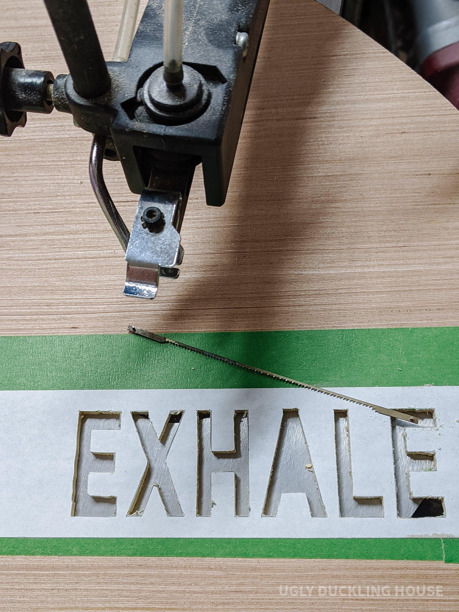 "cut out the word ""exhale"" using a scroll saw"