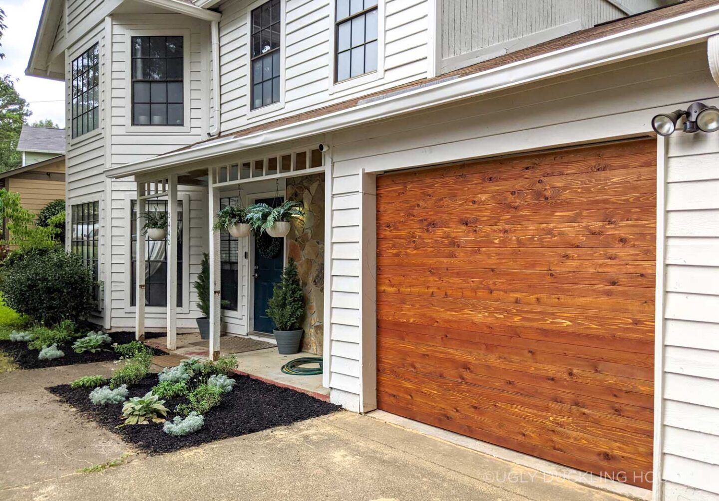 after - new cedar garage door and white siding